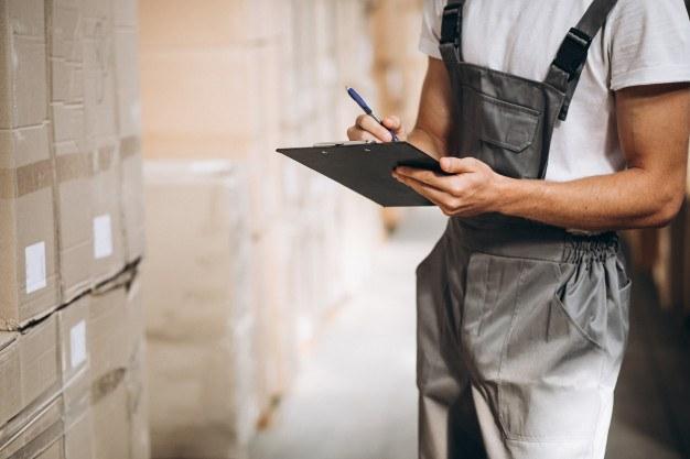 Egy férfi adminisztrálja a készletet egy raktárban